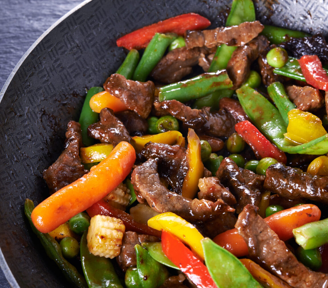 pan with stir fried beef and vegetables close up